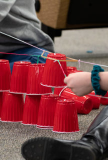 Stacking cups in a team using only strings
